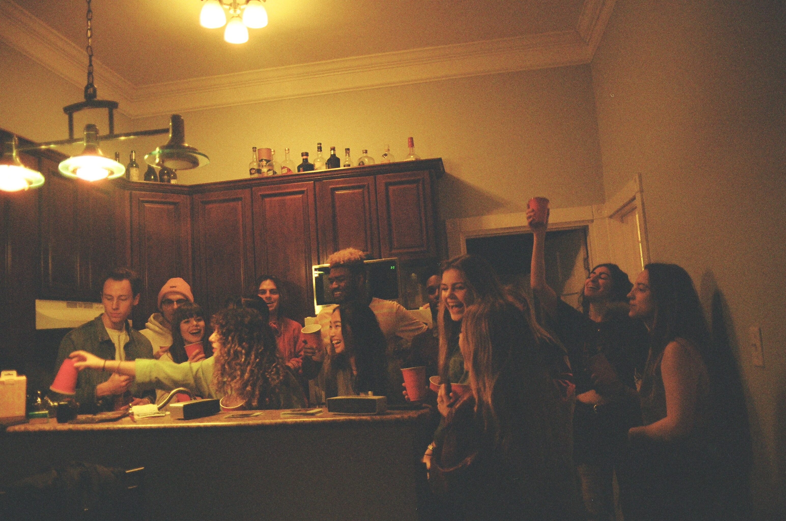 a bunch of young people in a kitchen at a party having drinks