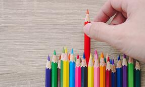 A series of colored pencils stacked next to each other and a hand selecting the red pencil