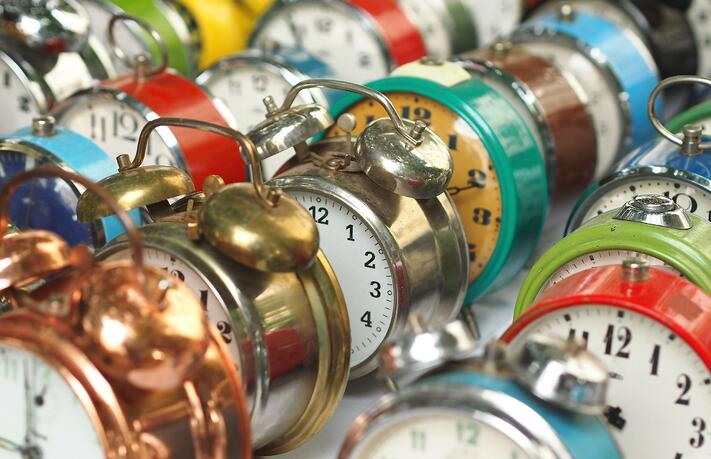 Several colorful old-fashioned alarm clocks, arranged diagonally
