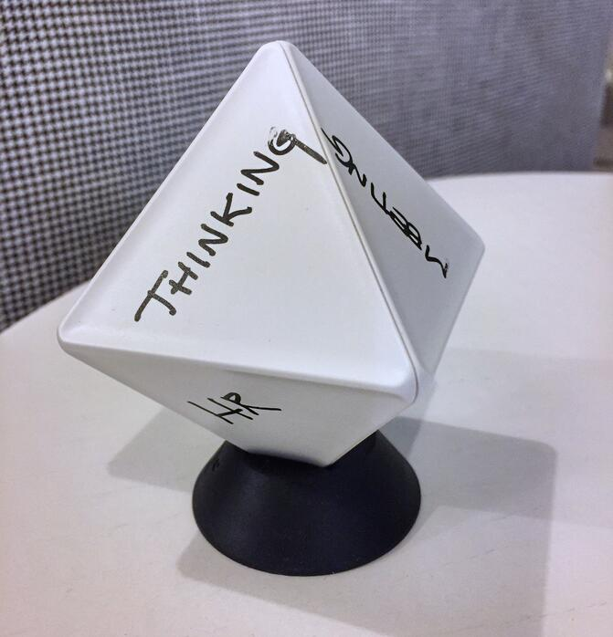 "A white, plastic, diamond-like shaped device atop a black circular mount with ""Thinking"" ""Meeting"" and ""HR"" written on it"