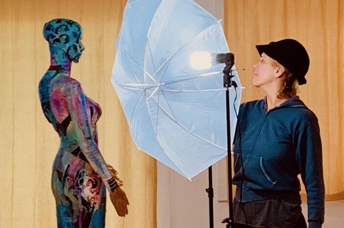 Annie Wood faces one of her painted mannequins with photo umbrella in background
