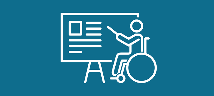 A person in a wheelchair teaching and pointing at information on a board