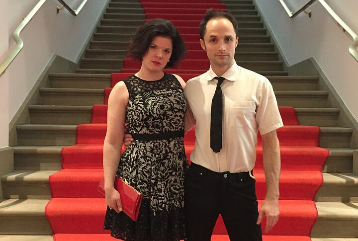 Susie Williams and TerryCrane stand in front of a stairway with red carpet