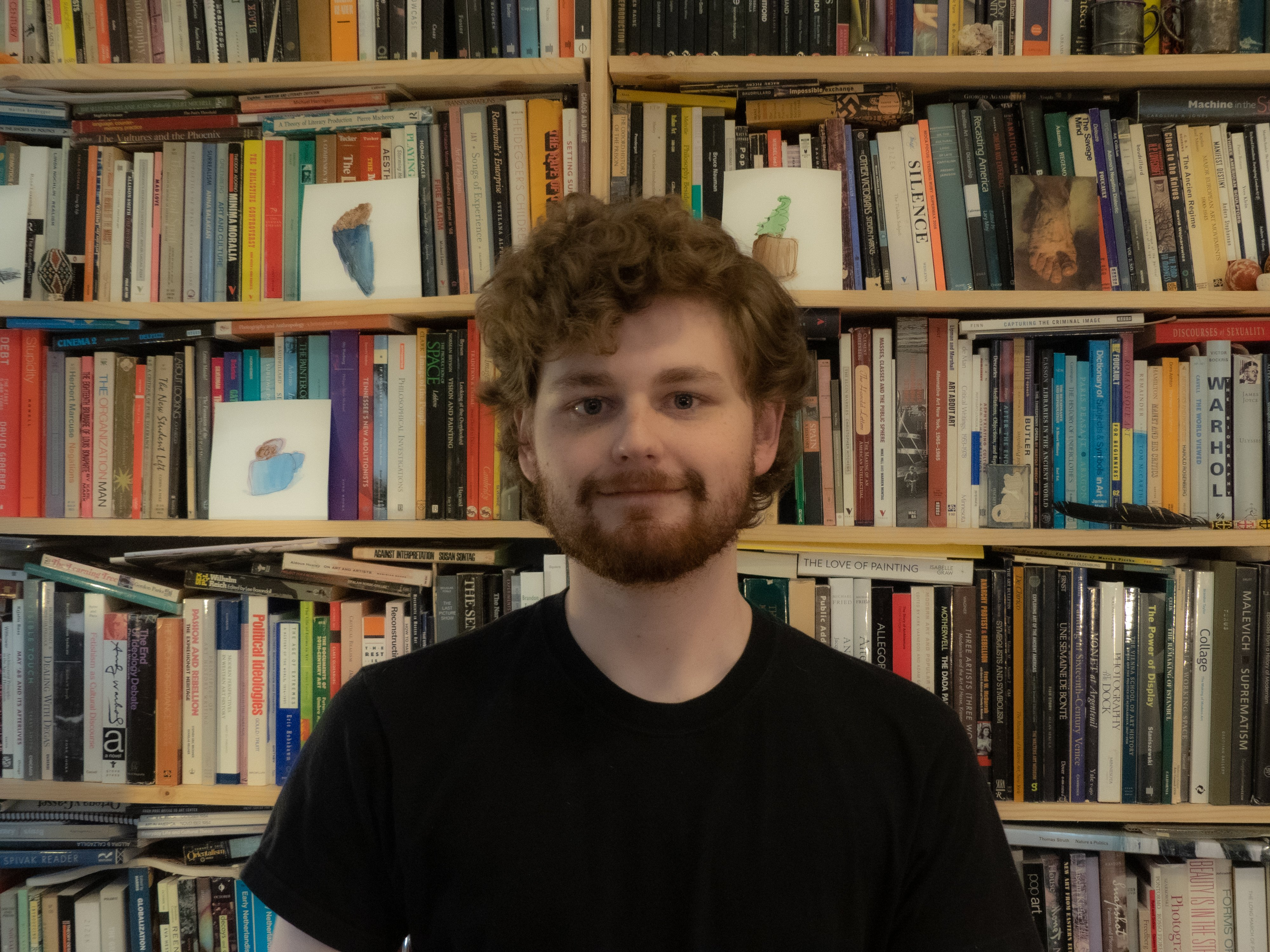A photo of Colo in front of full bookshelves with full head of hair and beard wearing a black tee