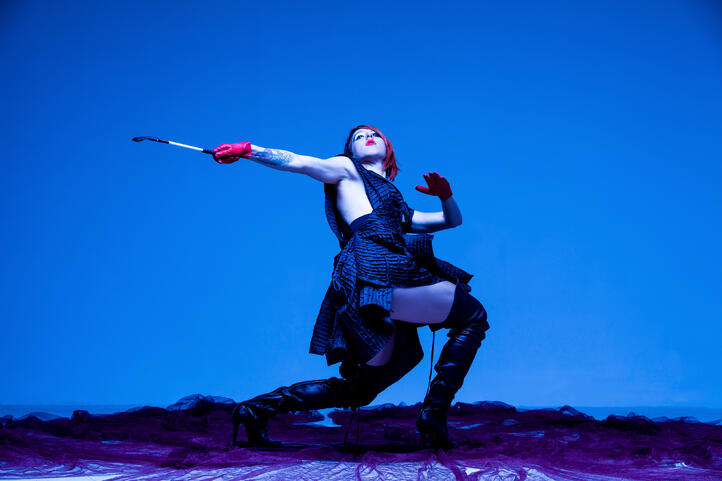 Agatha Wright, Founder of Fluxus Haus, dances against blue background