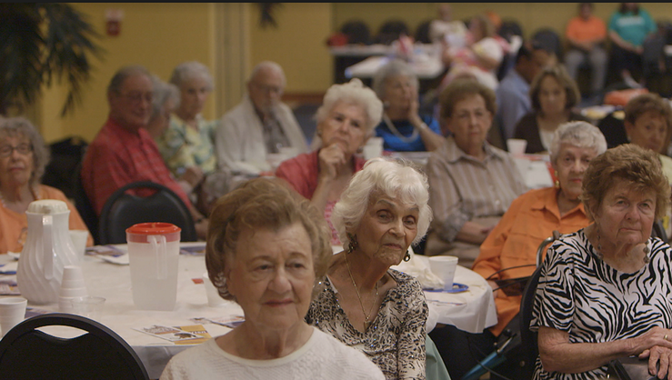 "A still of elders in a room listening from ""A Greater Society"""