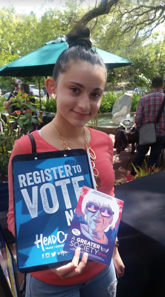 a young person holds the flyer for the movie and a poster encouraging people to register to vote