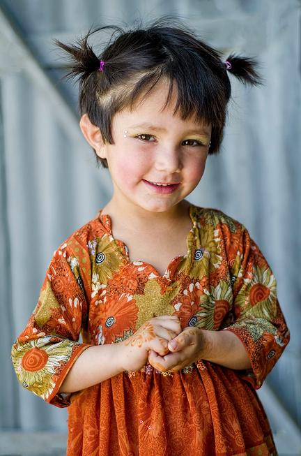 Pashtun kid smiling at camera, hair in little pigtails with rhinestones on face