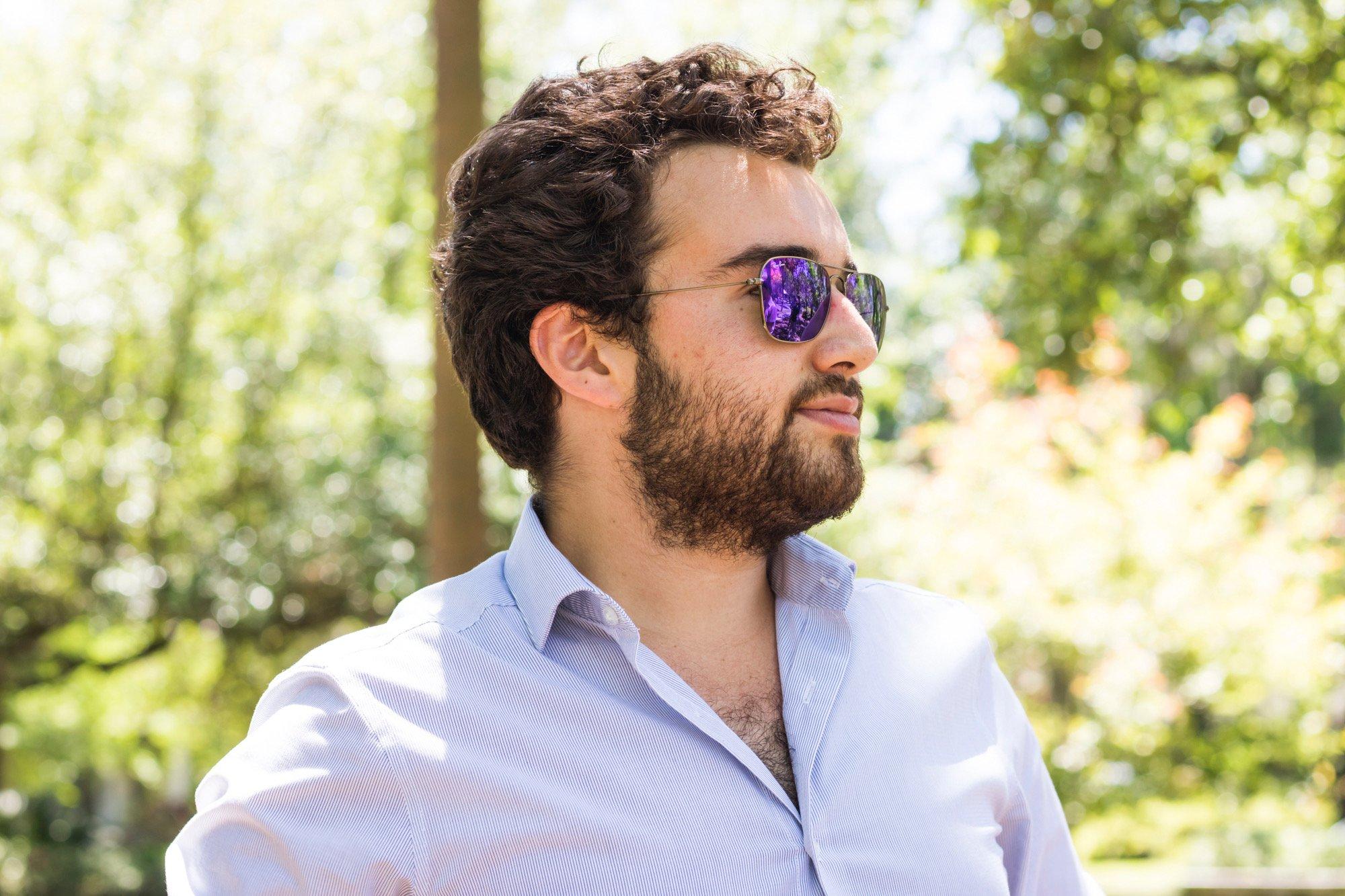 A bearded Joshua Prem with shades on, profile shot