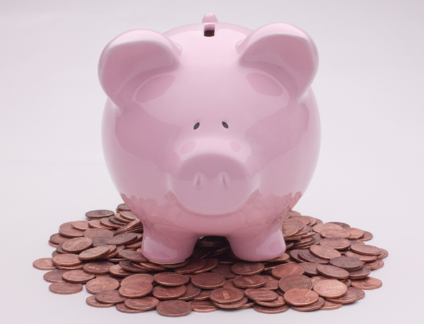 A piggy bank standing on top of a pile of pennies.