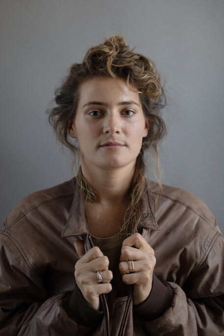 Meryl Jones Williams (Writer & Director) Headshot, in brown leather jacket, holding the lapels