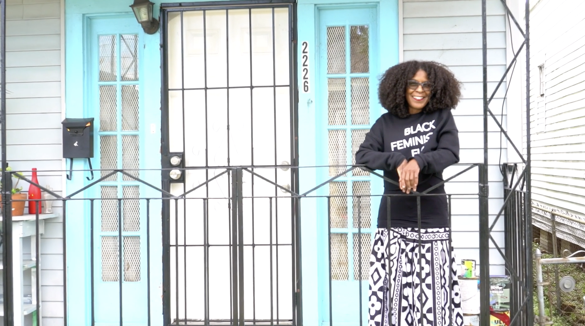 Kai standing in front of her studio with sky blue colored doors, wearing a sweatshirt that reads 'Black Feminist'