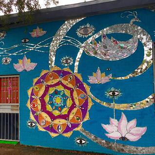 A wall painted blue with a mosaic mural, colored in pink, orange, and silver