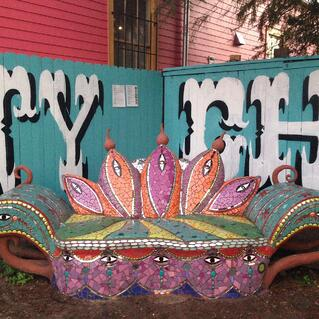 A couch-like seat completely covered in mosaic, colored in orange, pink, red, and blue