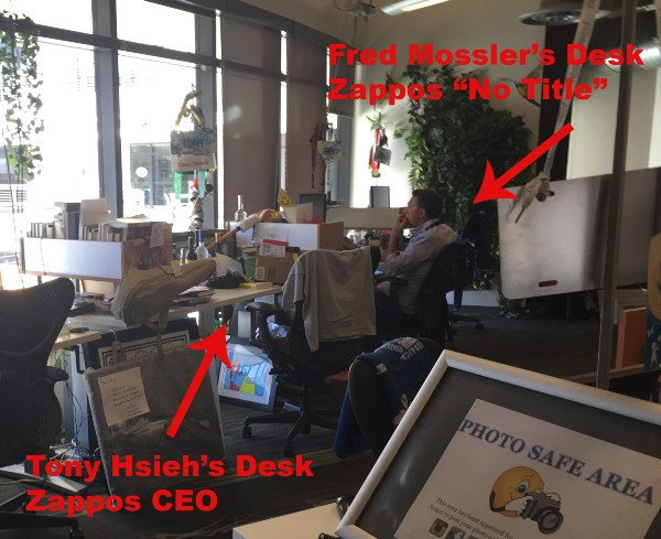"""Zappos Desks in office space with arrows pointing to CEO desk and """"no title"""" desk"""