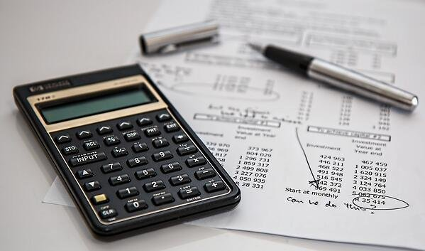 A calculator, pen, and financial document.