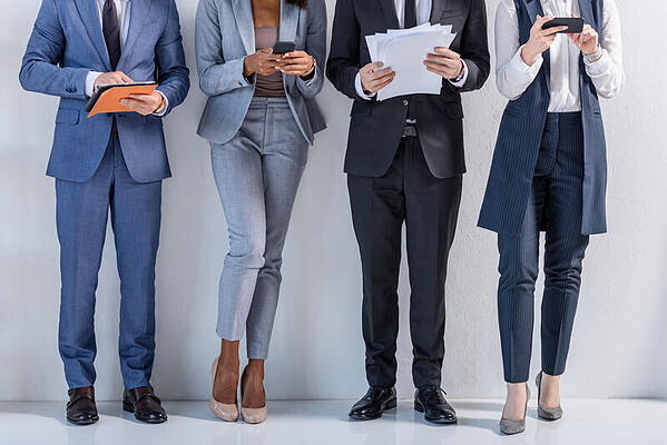 People standing in a row in suits considering whether or not virtual work suits them.