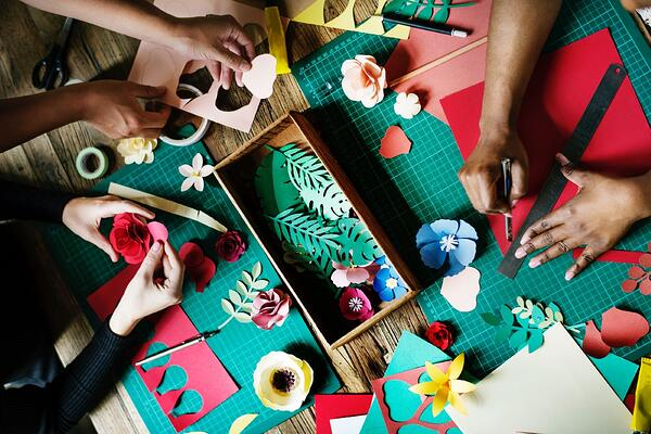 People cutting crafts to make holiday ornaments.